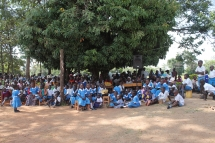 Eltern und SchülerInnen auf dem Schulgelände. Unter diesem Baum wurde unterrichtet, bevor Nashon Omondi die ersten Schulgebäude bauen lies.