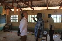 Charles Opondo zeigt Alois Stimpfle die Klassenräume